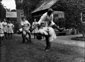 A group of the Women's Lad Army members playing leapfrog after their efficiency test, pictured at Tregavethan Farm. Photographer: A W Jordan. © From the collection of the RIC (TRURI-1972-2-339).
