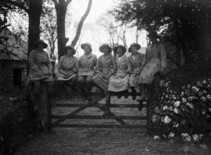 Seven members of the Women's Land Army sitting on a gate at Tregavethan Farm, facing towards the camera. The names of the women are as follows, left to right: Ms Trejeweth, unknown, Ms Brown, Ms I Crowther, Mrs Ford, Md Dorothy Phyllis Martin, unknown. The women's uniform consists of boots, gaiters, felt hats and pale fabric overalls. Photographer: A W Jordan. © From the collection of the RIC (TRURI-1972-2-82).