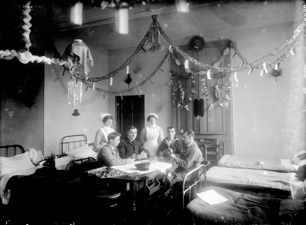 Nurses and patients (one sailor) playing cards in the ward at the Royal Cornwall Infirmary, Christmas 1915. Photographer: A W Jordan. © From the collection of the RIC.